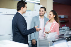 Assistant helping customers to choose. Experienced shop assistant helping positive customers to choose household appliances Royalty Free Stock Images