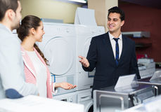 Assistant helping customers to choose. Experienced shop assistant helping smiling customers to choose household appliances Stock Images
