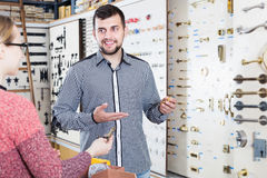 Assistant helping female customer to choose door handles Royalty Free Stock Image