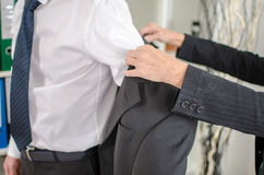 Assistant helping his boss to put his jacket Royalty Free Stock Images