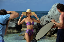 Assistant helping photographer to control light over swimsuit model. Photographers assistant helping photographer to control light over swimsuit model at Royalty Free Stock Image