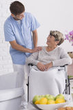 Assistant helping senior on wheelchair Stock Images