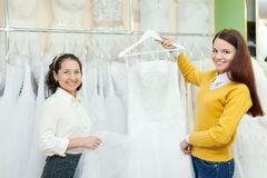 Assistant  helps the bride in choosing bridal gown Stock Photo