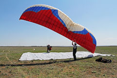 Assistant helps the paraglider to straighten the paraplane before the flight in Volgograd Royalty Free Stock Photos