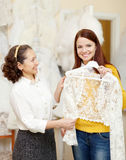 Assistant  helps to girl chooses  bridal clothes Stock Photo