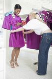 Assistant Helps Woman Consider Fuschia Raincoat Stock Photography