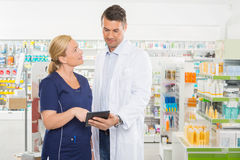 Assistant Looking At Pharmacist Using Digital Stock Photos