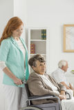 Assistant looks on elder woman Stock Photography