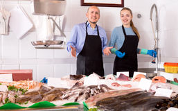 Assistant and mature seller offering fresh fish Stock Image