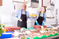 Assistant and mature seller offering frozen fish Stock Photo