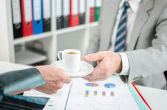 Assistant offering coffee to her boss Stock Photography