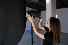 Assistant of photographer adjust light in studio. Beautiful woman with camera is setting photographing equipment getting ready for a photo shoot stock photography