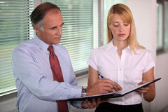 Assistant presenting boss with document Royalty Free Stock Photography