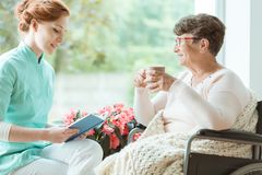 Assistant reading book to elder. Assistant in blue uniform reading a book to elder women in wheelchair in a hospital room stock photo