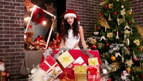 Assistant of Santa Claus shows many Christmas gifts stock video footage