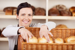 Assistant selecting rolls in a bakery. Smiling attractive female assistant selecting rolls in a bakery from a large wicker basket and smiling at the camera Stock Photos