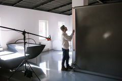 Assistant setting equipment in photostudio Royalty Free Stock Photos