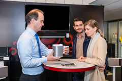 Assistant Showing Compact Speaker To Couple In Shop Royalty Free Stock Photo