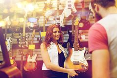 Assistant showing customer guitar at music store Royalty Free Stock Images