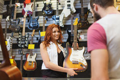 Assistant showing customer guitar at music store Stock Photo