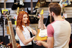 Assistant showing customer guitar at music store Royalty Free Stock Image