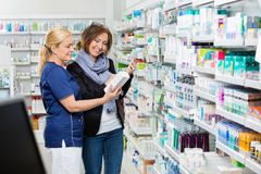 Assistant Showing Product To Customer Holding Cell. Smiling female assistant showing product to customer holding cell phone in pharmacy Royalty Free Stock Image