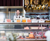Assistant showing sorts of meat in butcher's store Stock Images