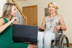 Assistant social et femme handicapée avec l'ordinateur portable Photo libre de droits