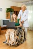 Assistant social et invalide avec l'ordinateur portable Photo libre de droits