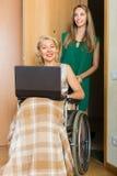 Assistant social et invalide avec l'ordinateur portable Image stock
