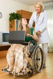 Assistant social et invalide avec l'ordinateur portable Images stock