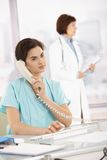 Assistant taking phone call for medical doctor Stock Photos
