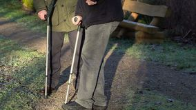 Assistant try to help disabled man on crutches stock footage