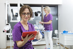 Assistant Using Digital Tablet While Colleague Working At Dentis. Female assistant using digital tablet while colleague working at dentistry stock photo