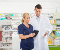 Assistant Using Digital Tablet While Pharmacist Royalty Free Stock Photography