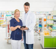 Assistant Using Digital Tablet With Pharmacist Royalty Free Stock Photos