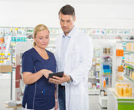 Assistant Using Tablet Computer With Pharmacist Royalty Free Stock Photography