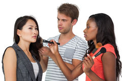 Assistants applying make-up to female model. Over white background stock photo