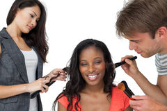 Assistants applying make-up to a female model Stock Photo