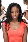 Assistants applying make-up to a female model Royalty Free Stock Photo