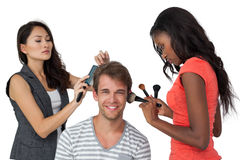 Assistants applying make-up to male model Royalty Free Stock Photo