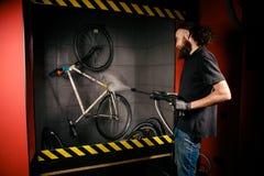 Assiste il lavaggio professionale di una bicicletta nell'officina Primo piano di giovane uomo alla moda caucasico della mano che  fotografia stock