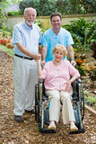 Assisted Living. Disabled senior woman and her husband with a male nurse on the grounds of an assisted living facility. Focus on the woman royalty free stock photography