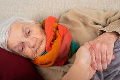 Assisted living. Close up portrait of elderly wrinkled woman lying on the couch, wearing colorful scarf, holding carer`s hand - aid, assisted living stock photos