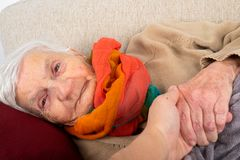 Assisted living. Close up portrait of elderly wrinkled woman lying on the couch, wearing colorful scarf, holding carer`s hand - aid, assisted living stock photography