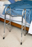Assisted Living Nursing Home Concept. A medical walker aid sits next to a bed for an assisted living or nursing home concept of the elderly royalty free stock photography