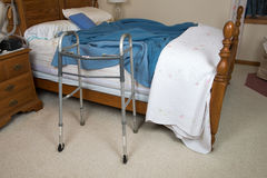 Assisted Living Nursing Home Concept. A medical walker aid sits next to a bed for an assisted living or nursing home concept of the elderly stock photography