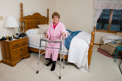 Assisted Living Nursing Home Elderly Woman. An old, elderly, senior woman sits on her bed with a medical walker aid. The female is happy and has a smile on her royalty free stock photos
