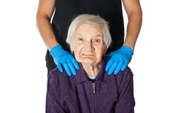 Assisted living. Portrait of a cheerful senior woman having dementia disease, assisted by a male caregiver. Man`s hands on patient`s shoulder stock image