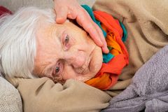 Assisted living - sad elderly woman. Close up portrait of a sad elderly wrinkled woman lying on the couch, wearing colorful scarf - caregiver`s hand touching her royalty free stock photo
